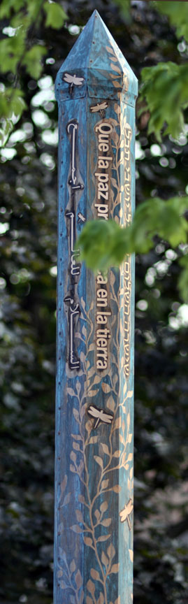 Copper Peace Pole with vines and peace messages etched into its patina