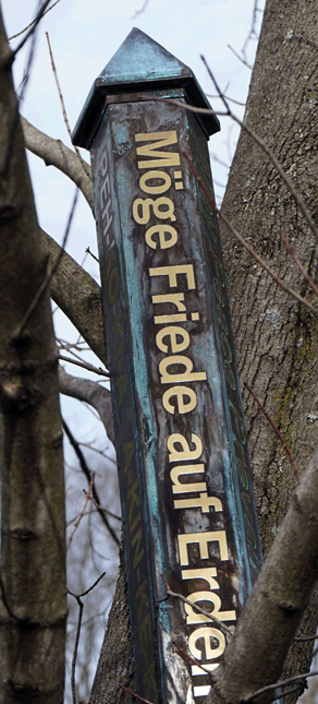 Copper peace pole temporarily leaning on a tree