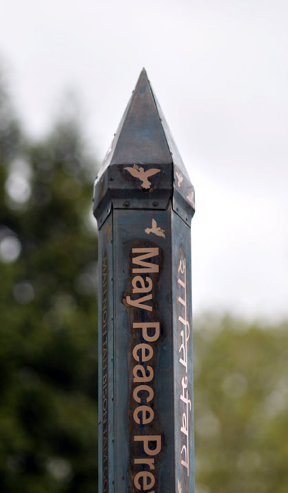 Copper peace pole etched with doves and peace messages in many languages