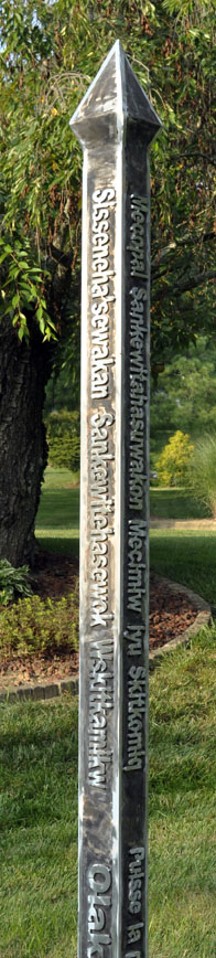 Peace Pole made of aluminum standing in a yard