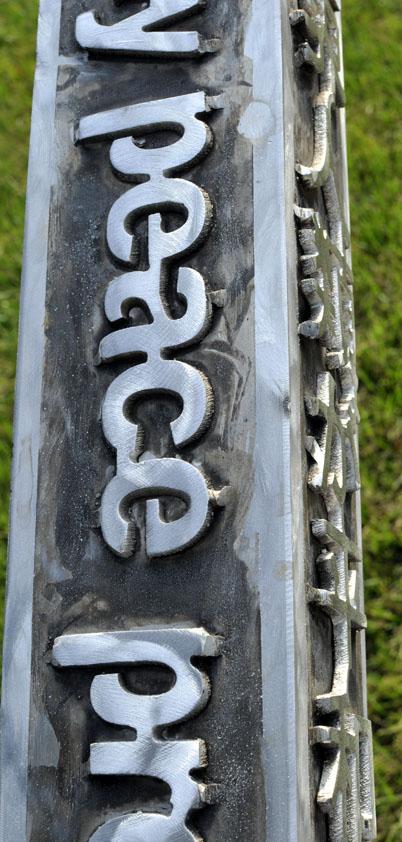Closeup view of raised text on aluminum peace pole